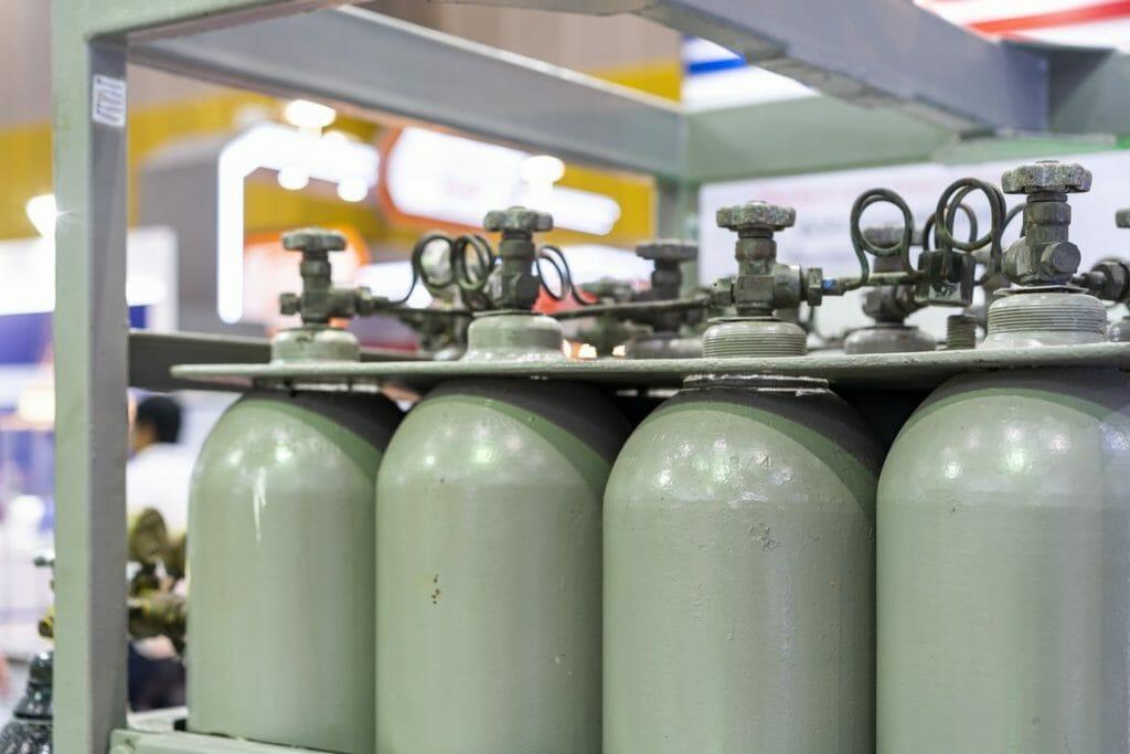 Graue CO2 Flaschen im Bündel in Lagerkäfig