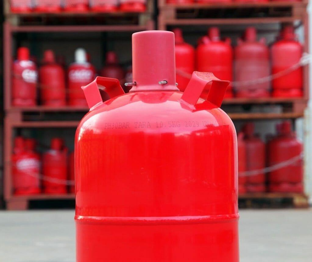 Rote Propangasflasche vor Gasflaschenlager