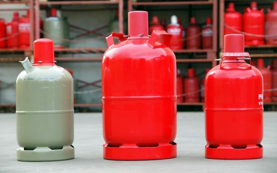 Rote Pfandflaschen und graue Kauf Gasflaschen im Lager